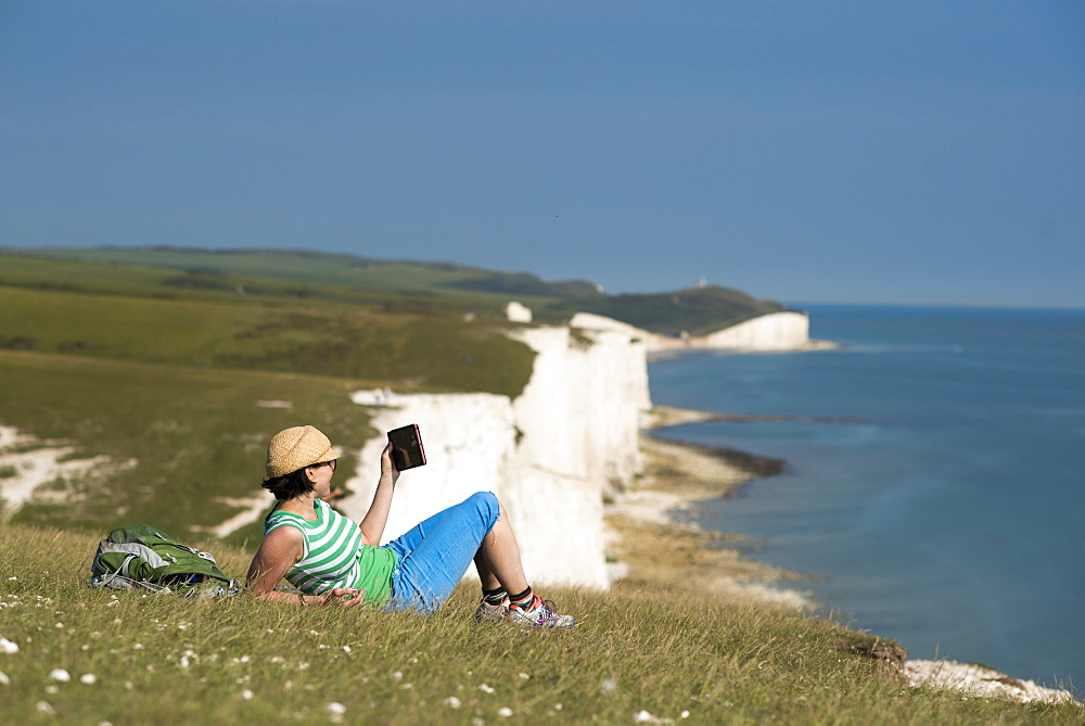 A woman reads her iPad on the cliffs with views of the Seven Sisters coastline in the distance, South Downs National Park, East Sussex, England, United Kingdom, Europe