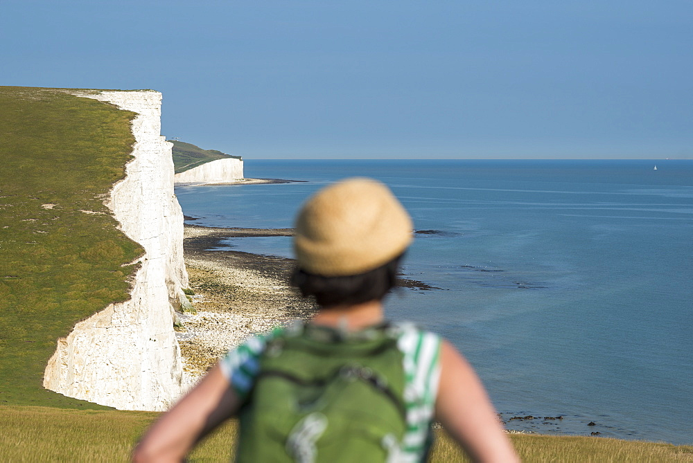 A woman looks out over the cliffs near Beachy Head with views of the Seven Sisters coastline in the distance in England
