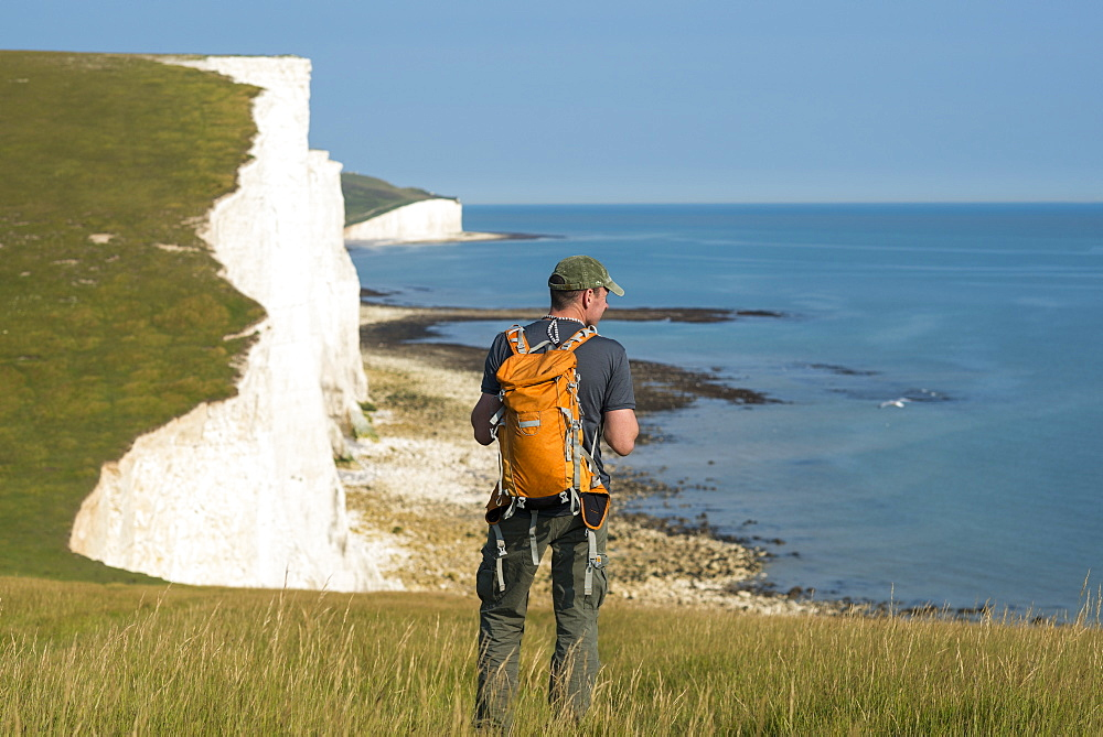 A man looks out over the chalk cliffs with views of the Seven Sisters coastline in the distance, South Downs National Park, East Sussex, England, United Kingdom, Europe