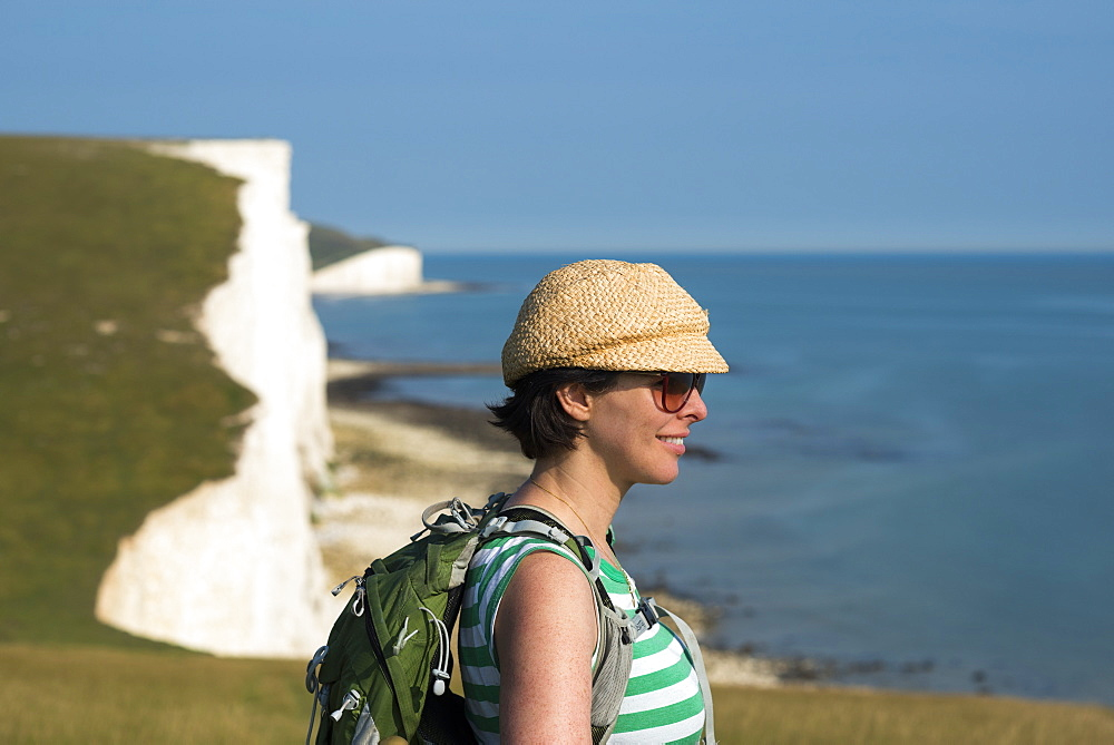 A woman looks out over the cliffs near Beachy Head with views of the Seven Sisters coastline, South Downs National Park, East Sussex, England, United Kingdom, Europe