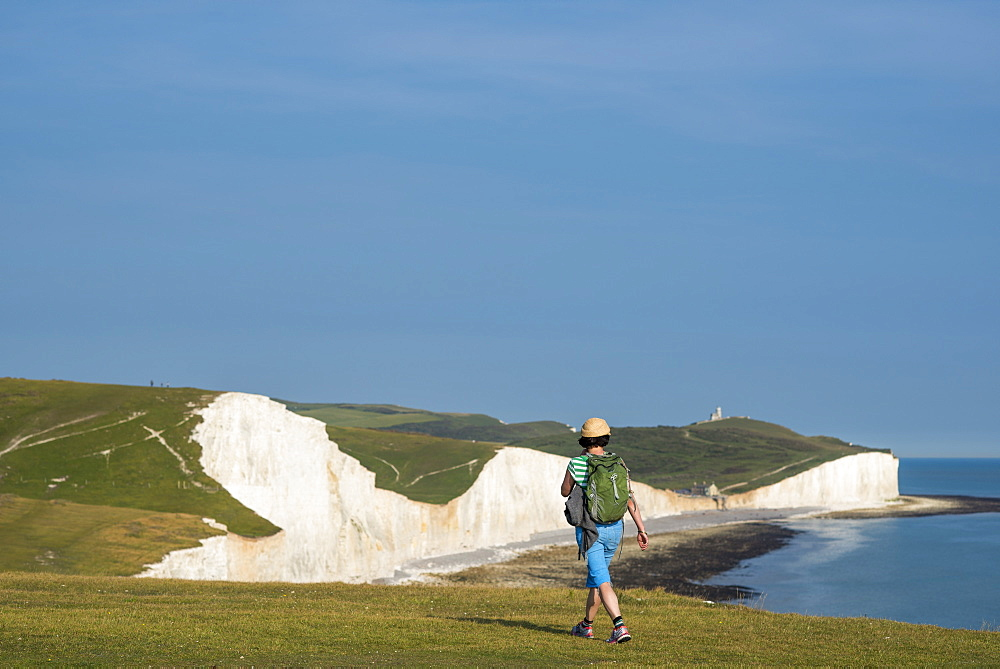 A woman walks along the cliffs near Beachy Head with views of the Seven Sisters coastline in the distance in England