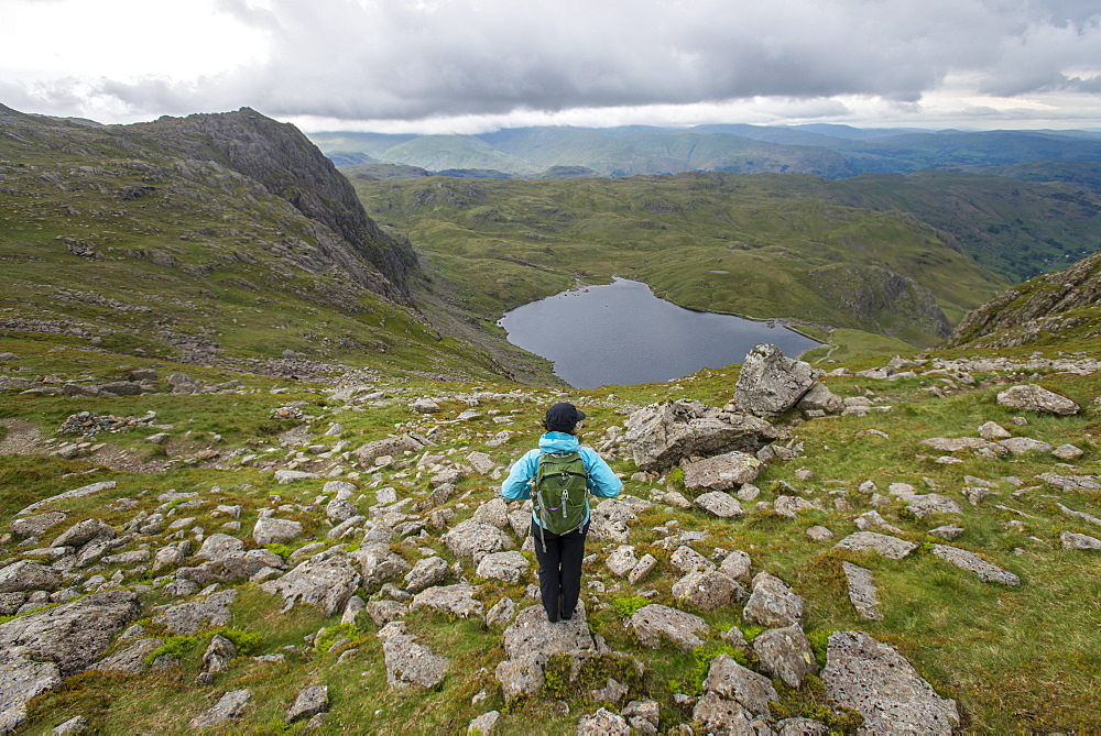 Walking in Great Langdale in The Lake District with a view of Stickle Tarn in the distance