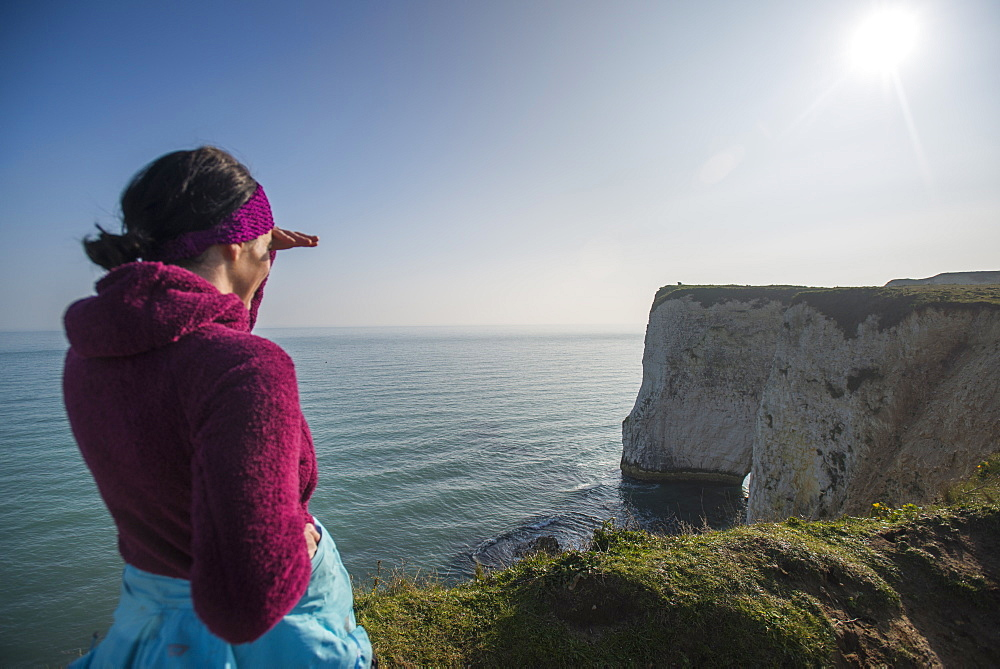 A woman looks out at Old Harry Rocks at Studland Bay in Dorset on the south coast of England