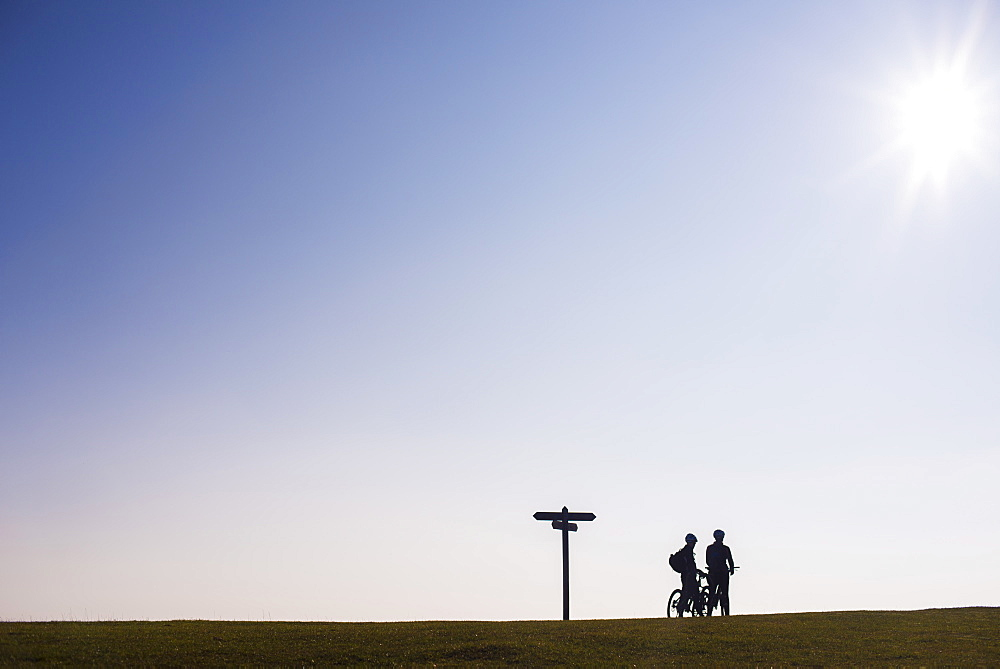 Cyclists in Dorset in the UK take a break on the brow of a hill at sunset in England