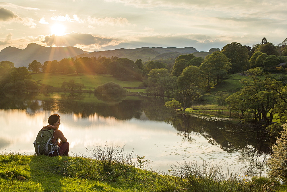 A woman looks out over Loughrigg Tarn near Ambleside, Lake District National Park, Cumbria, England, United Kingdom, Europe