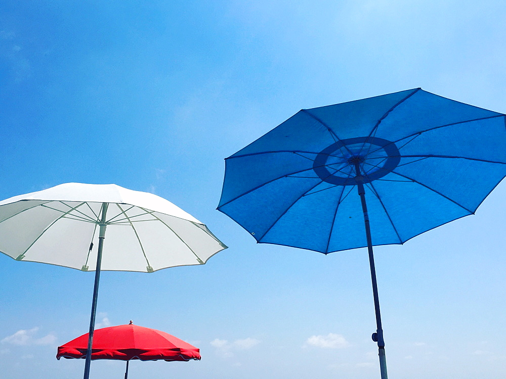 Red, white and blue beach parasols against a blue sky, Nice, Alpes Maritimes, Cote d'Azur, French Riviera, Provence, France, Europe