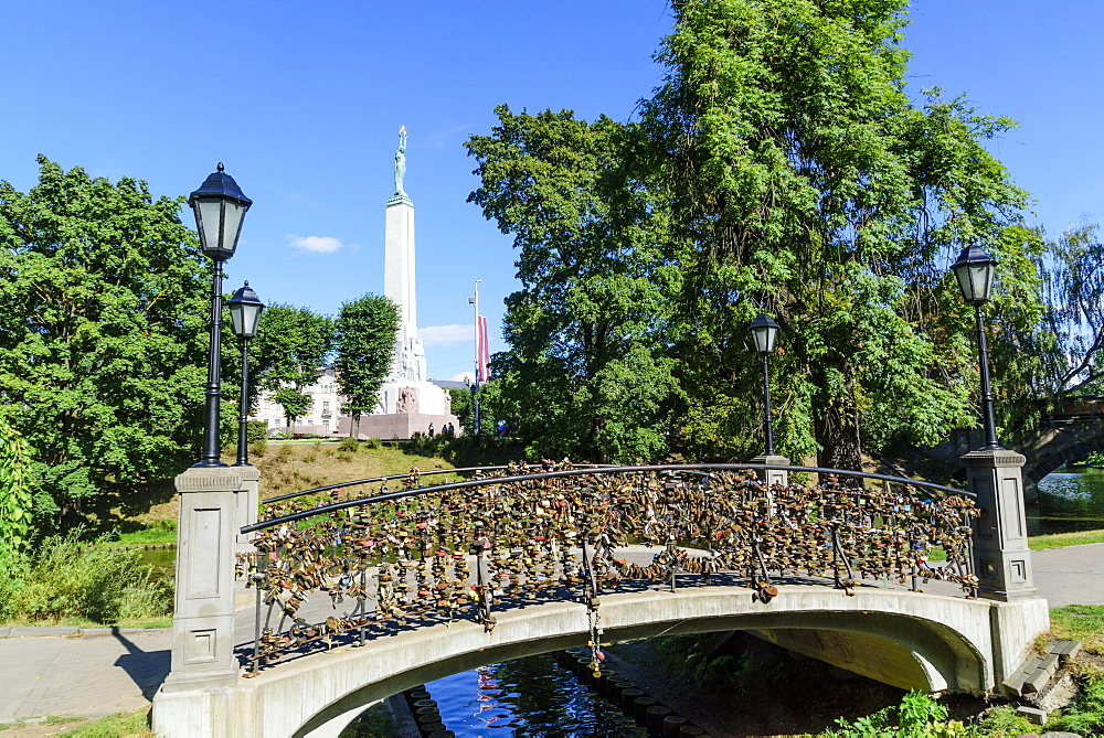 Freedom Monument and bridge with love lockets, Bastejkalna Parks, Riga, Latvia, Europe