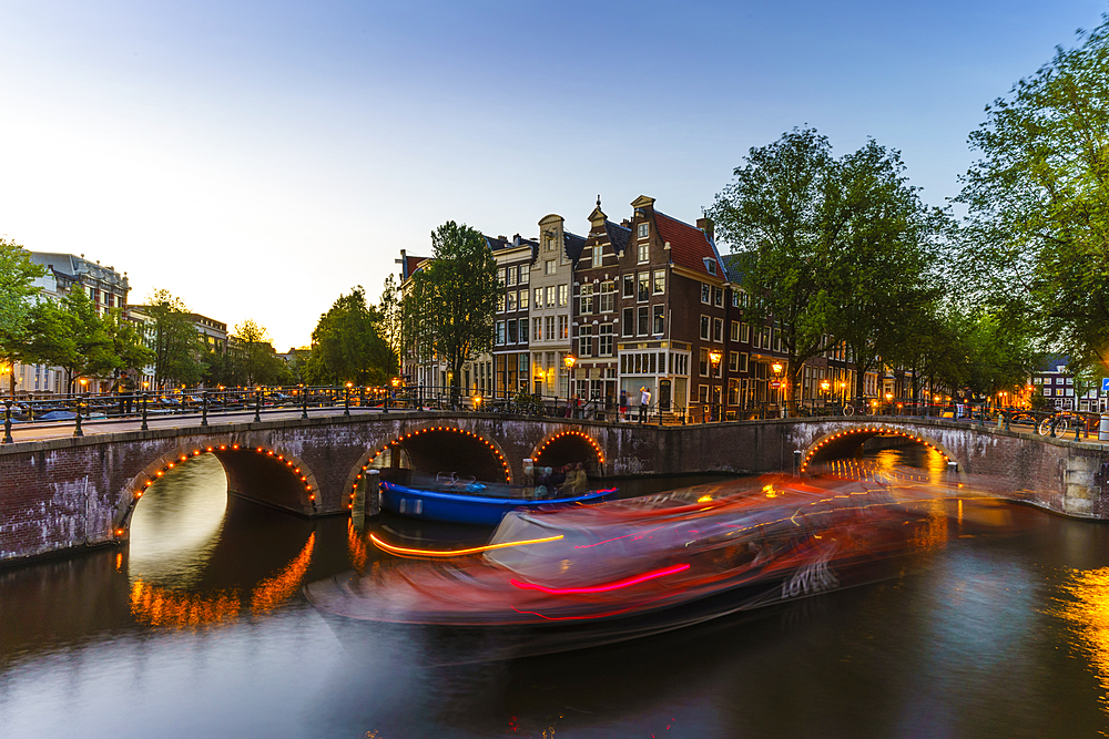 Keizergracht Canal at dusk, trailing light blur from a tourist boat, Amsterdam, North Holland, The Netherlands, Europe