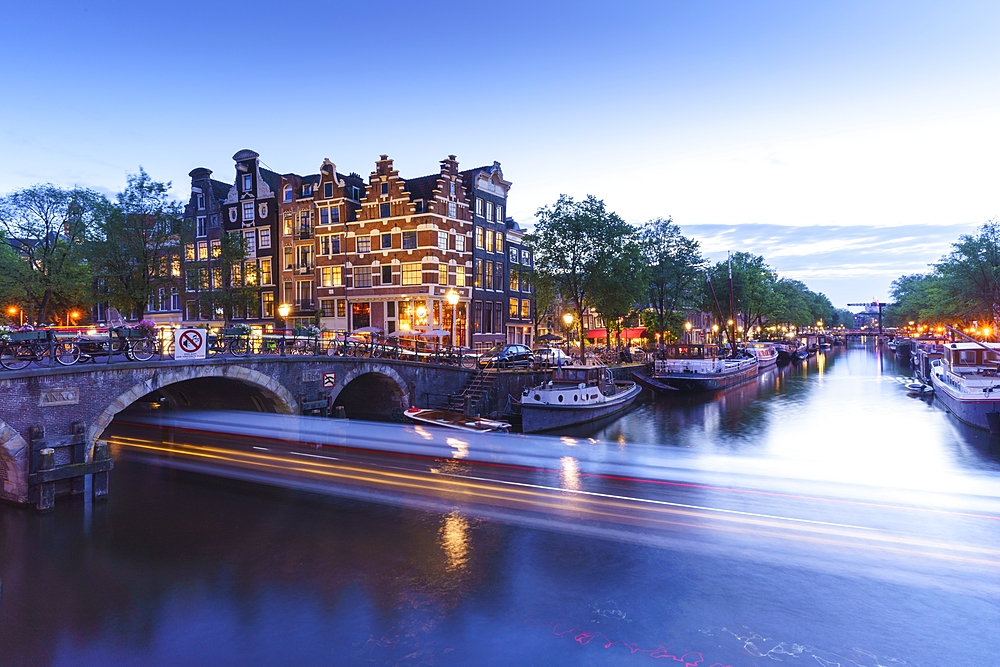 Dusk on Brouwersgracht Canal with trailing light from a tourist boat passing under a bridge, Amsterdam, North Holland, The Netherlands, Europe