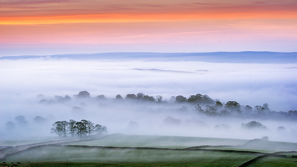 Mist rising over East Halton and Embsay at sunrise, in Lower Wharfedale, North Yorkshire, Yorkshire, England, United Kingdom, Europe