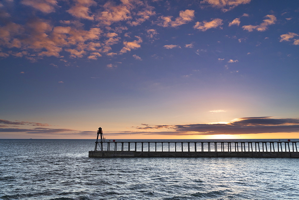 Sunrise over the North Sea and Whitby harbour and piers in late summer.
