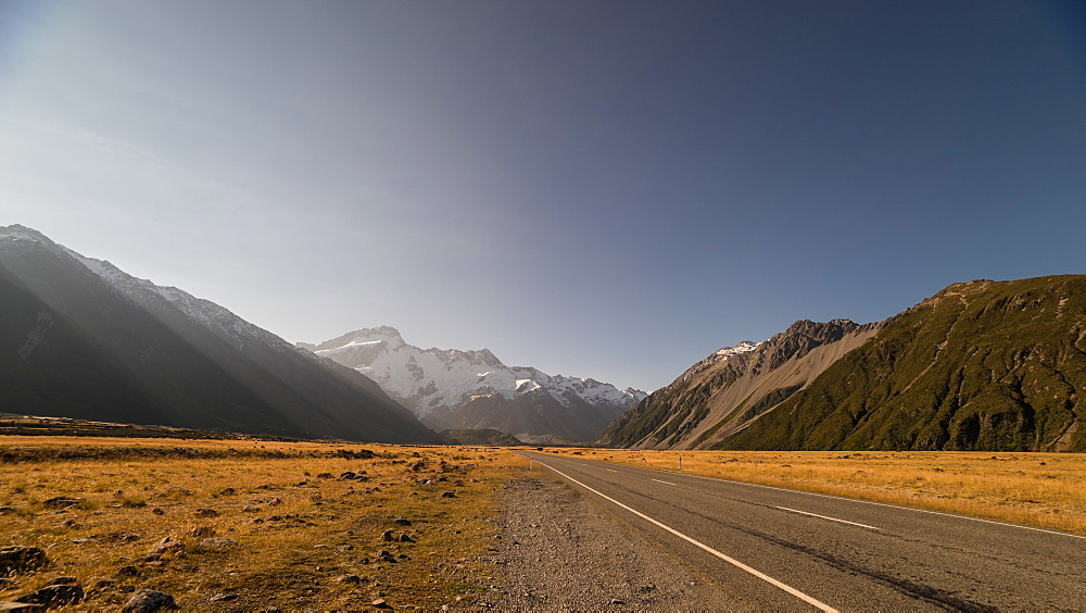 Late afternoon sun over a long straight road into the mountains, South Island, New Zealand, Pacific - 1233-16