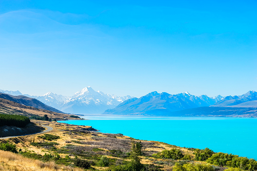 A road winds along the edge of a turquoise blue lake with mountains in the distance, South Island, New Zealand, Pacific - 1233-17