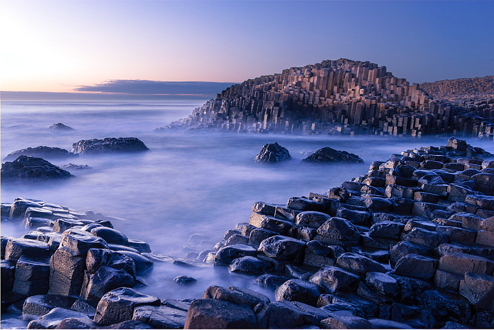 The Giant's Causeway rises out of the Atlantic late at night as the last light of the sun disappears below the horizon, County Antrim, Northern Ireland, United Kingdom, Europe