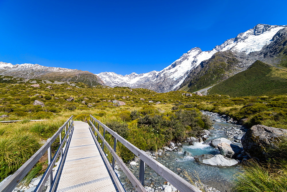 A hiking trail crosses wooden bridge over a creak high up in the mountains, South Island, New Zealand, Pacific