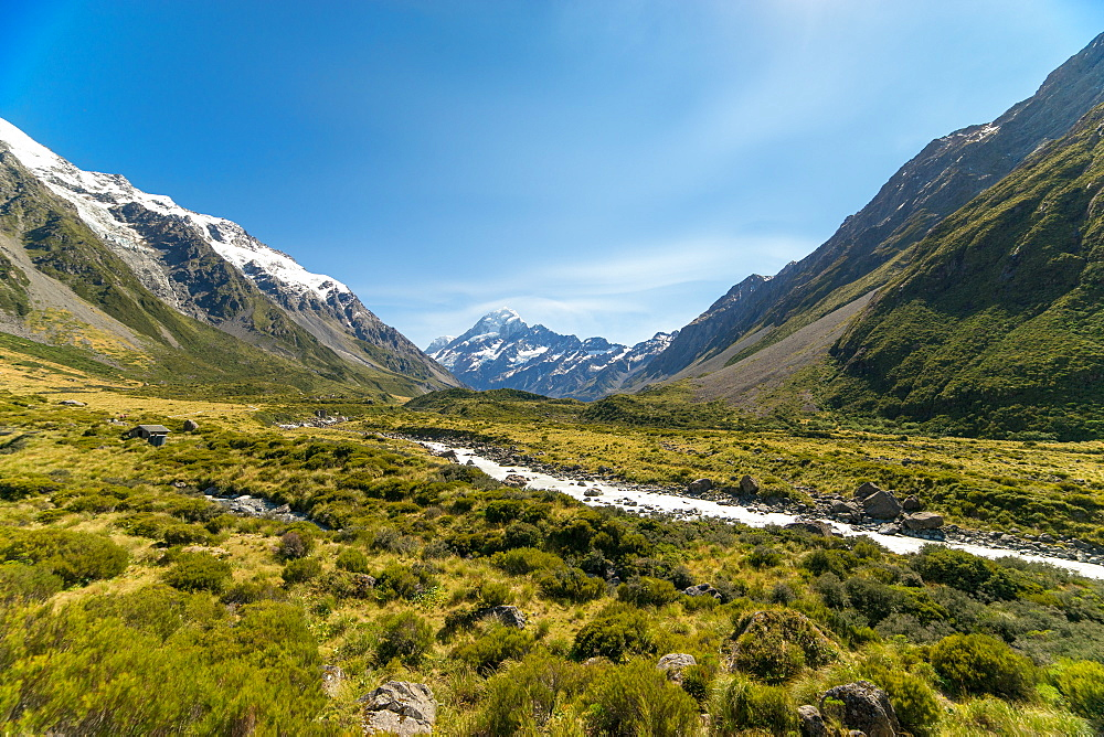 A glacier fed creek cuts through a green valley high in the mountains, South Island, New Zealand, Pacific