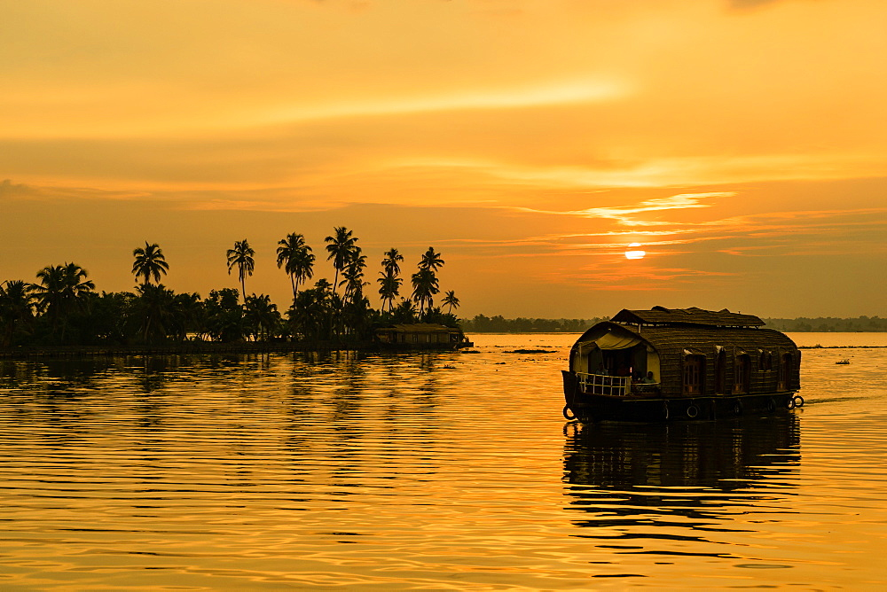 A traditional houseboat moves past the setting sun on the Kerala Backwaters, Kerala, India, Asia