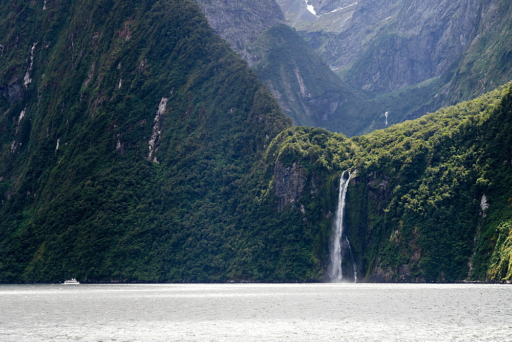 A sightseeing ship dwarfed by a tall waterfall in a fjord, South Island, New Zealand, Pacific