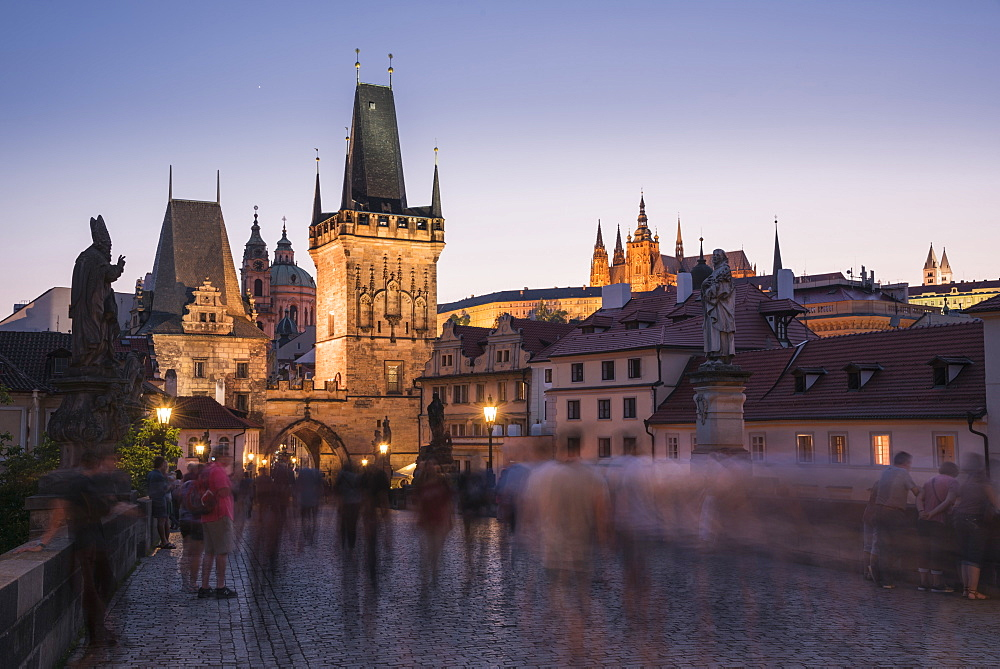 Charles Bridge, Lesser Towers, and Prague Castle at night with blurred pedestrians, UNESCO World Heritage Site, Prague, Czech Republic, Europe