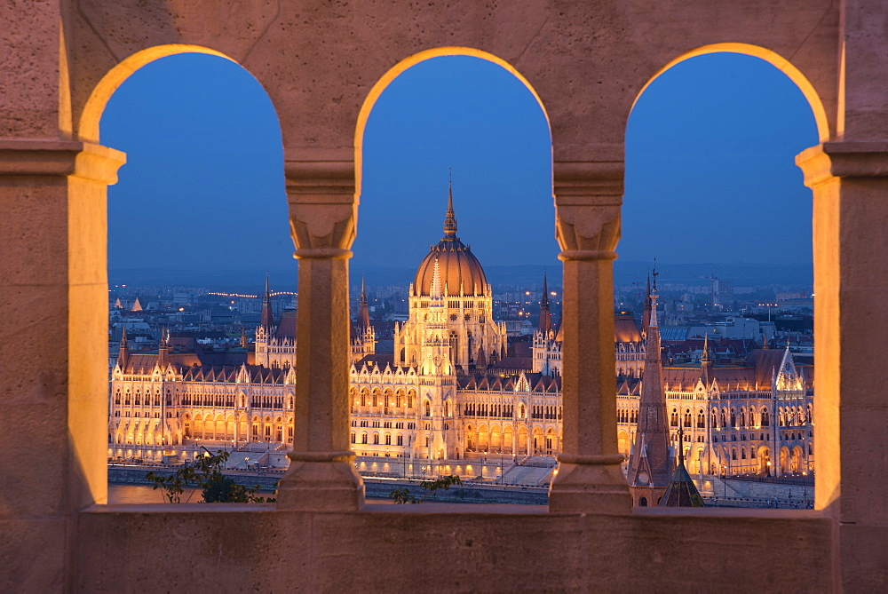 Hungarian Parliament at night, viewed from the columns and windows of the Fisherman's Bastion, UNESCO World Heritage Site, Budapest, Hungary, Europe