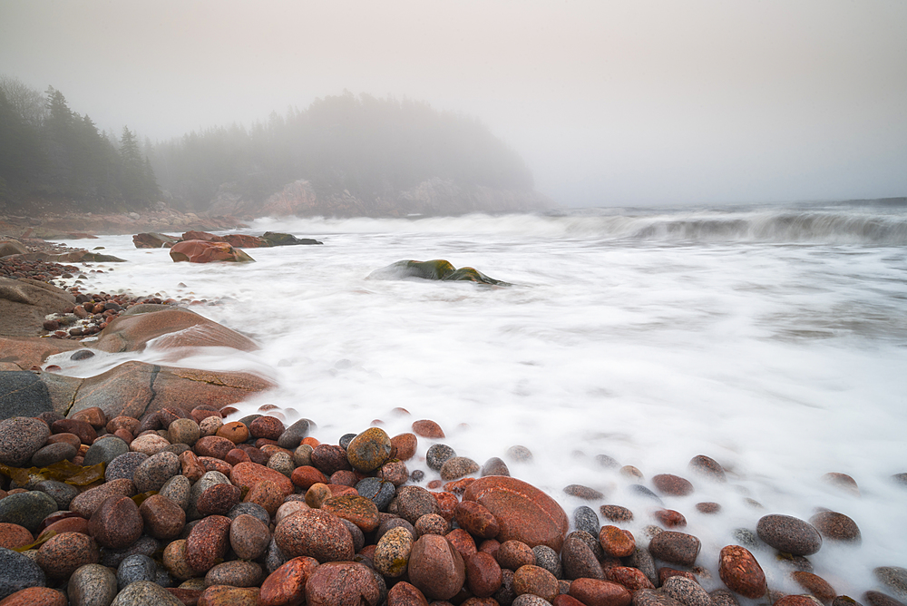 Long exposure of waves crashing on colourful pink rocks, Black Brook Cove Beach, Cape Breton, Nova Scotia, Canada