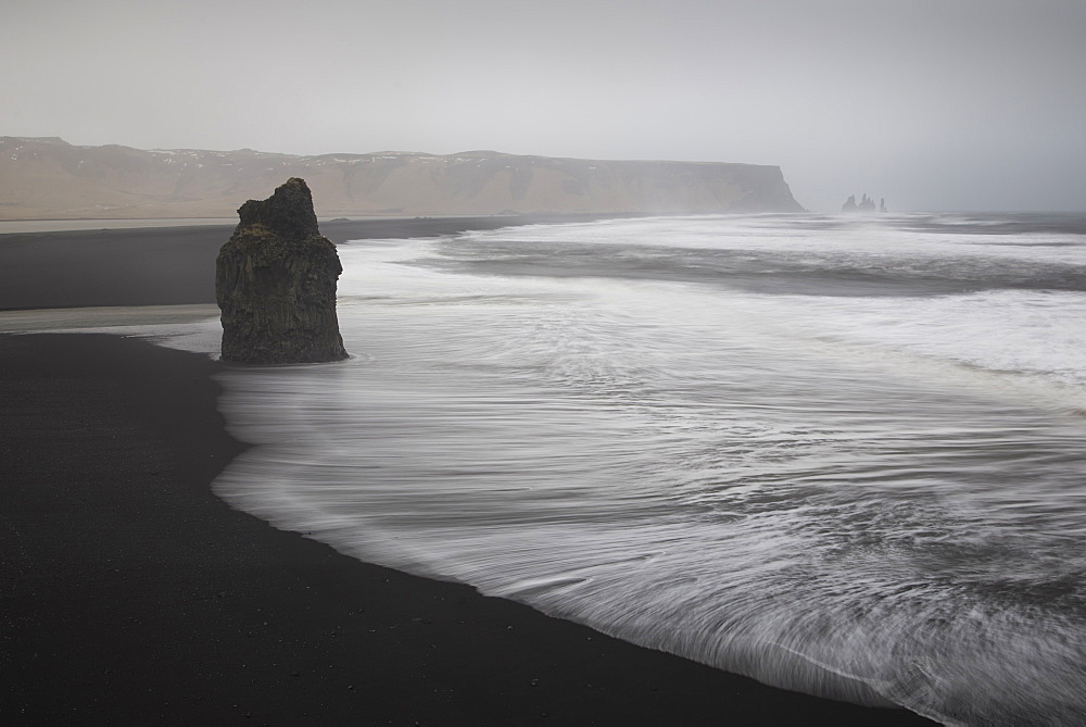 Reynisdrangar basalt rock columns and black sand beach in Vik, Iceland