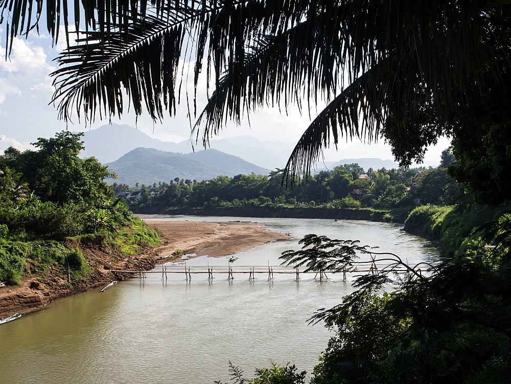 Nam Kang River with mountains, bamboo bridge, and palm trees, Luang Prabang, Laos, Indochina, Southeast Asia, Asia - 1242-211