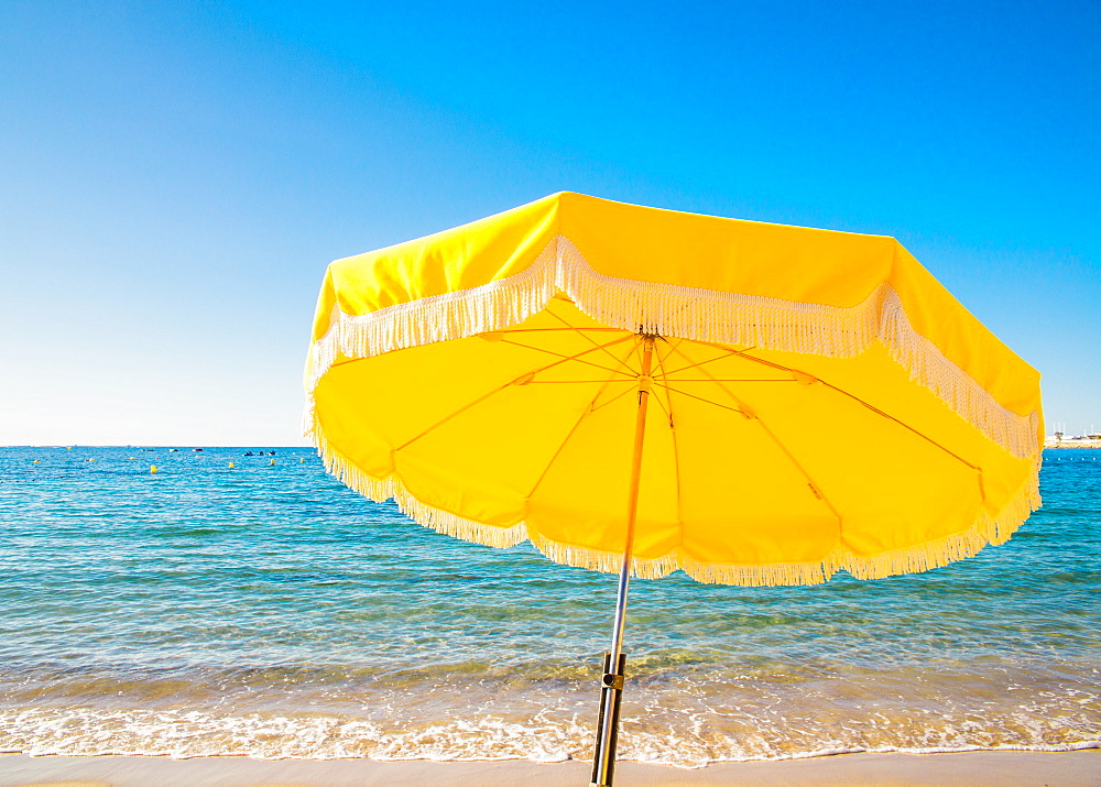 Giant yellow beach umbrella next to the ocean against a blue sky in Juan les Pins, Cote d'Azur, France