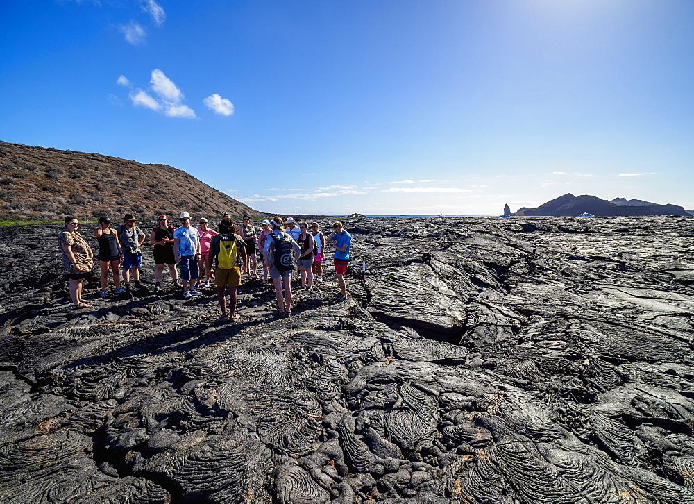Tourists visiting Lava field in Sullivan Bay, Santiago or James Island, Galapagos, Ecuador