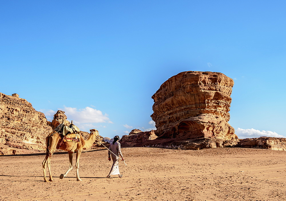 Bedouin walking with his camel, Wadi Rum, Aqaba Governorate, Jordan, Middle East