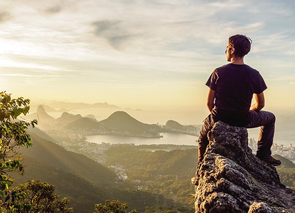 Hiker enjoying the view of Rio de Janeiro from Pedra da Proa, Tijuca Forest National Park, State of Rio de Janeiro, Brazil