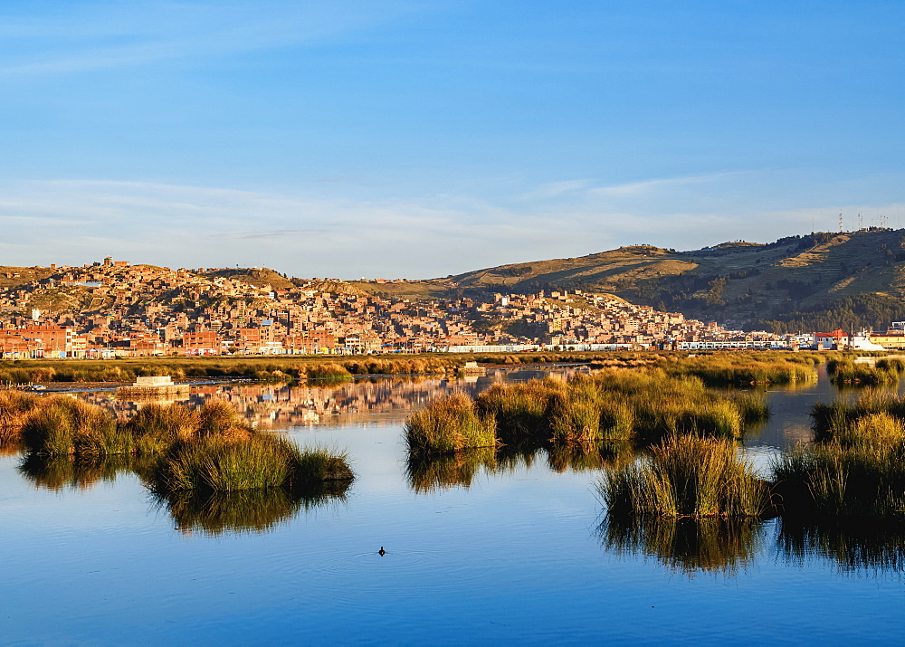 Lake Titicaca and cityscape of Puno at sunrise, Peru, South America