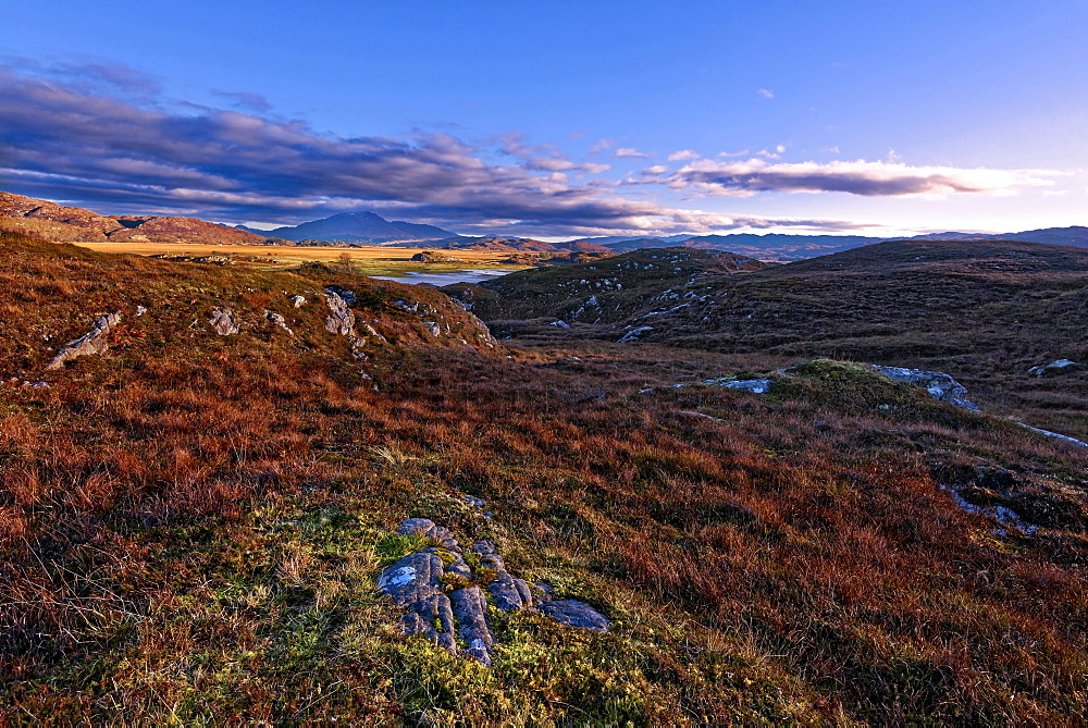 Autumn view of colorful grasses and rocks and misty mountains in the moors of the Scottish Highlands as the fading sun sets