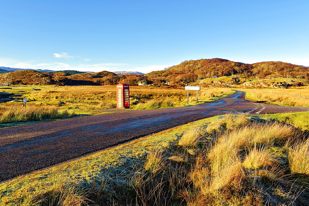 An autumn view of a red telephone box at the side of a quiet road in the remote Ardnamurchan moors of the Scottish Highlands