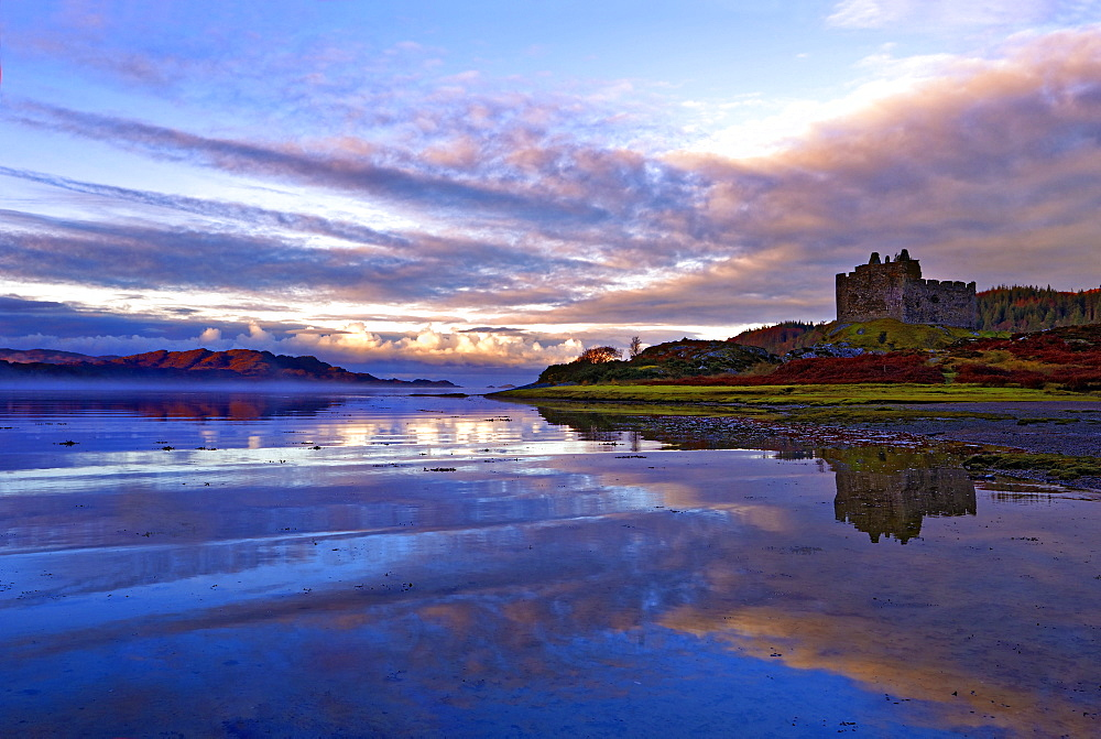 Early morning view of Castle Tioram and Loch Moidart as dawn breaks in a warm colorful sky to form attractive reflections, Highlands, Scotland, United Kingdom, Europe