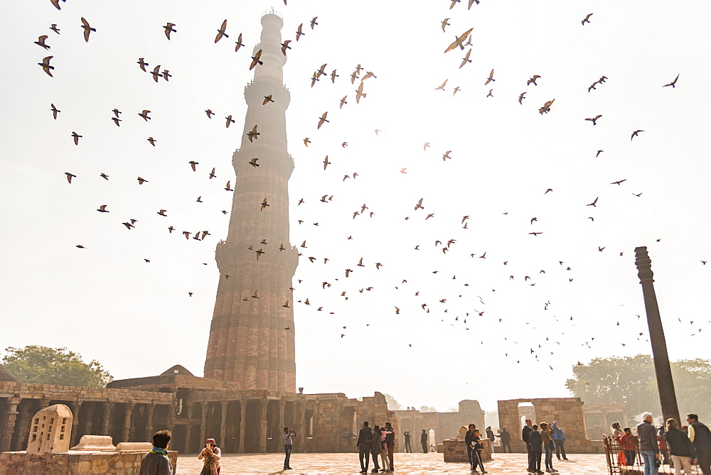Birds fly over visitors while they take photos of one another at Qutub Minar, UNESCO World Heritage Site, New Delhi, India, Asia