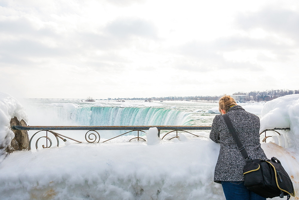 A lady takes a photograph of the Frozen Niagara Falls in March, Ontario, Canada, North America