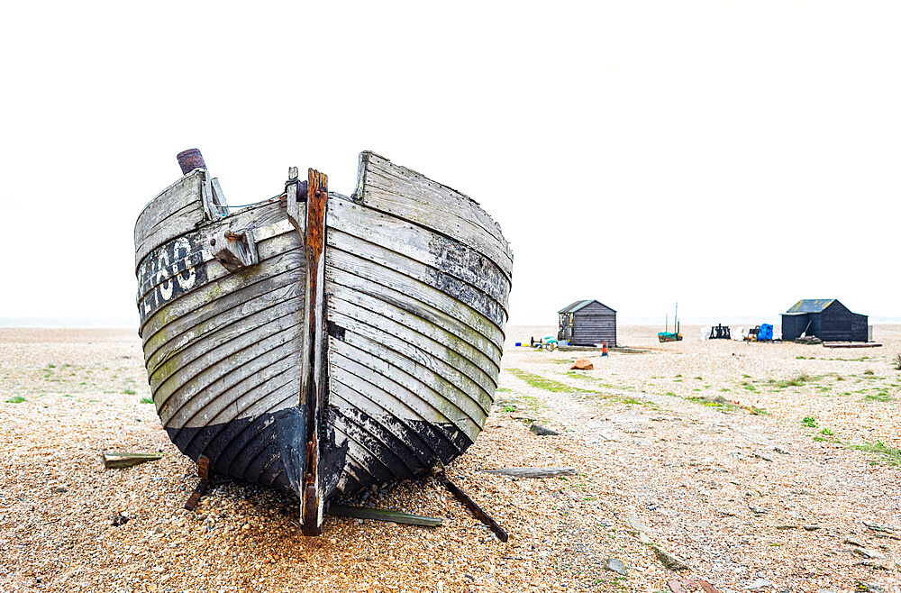 March 2019, Dungeness, Kent, England - The old fishing boat lies on the beach.with fishermans huts inthe background - 1247-210