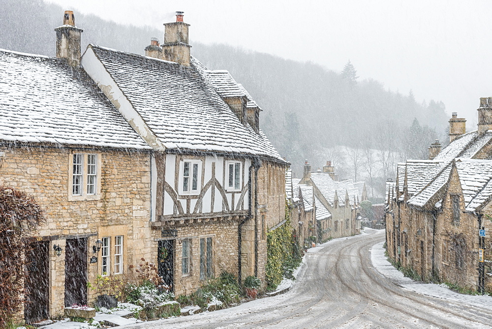 Looking down the quintessential English village of Castle Combe in the snow, Wiltshire, England, United Kingdom, Europe - 1247-49