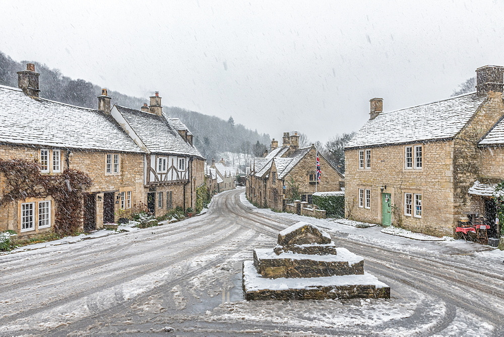 Looking down the quintessential English village of Castle Combe in the snow, Wiltshire, England, United Kingdom, Europe - 1247-50