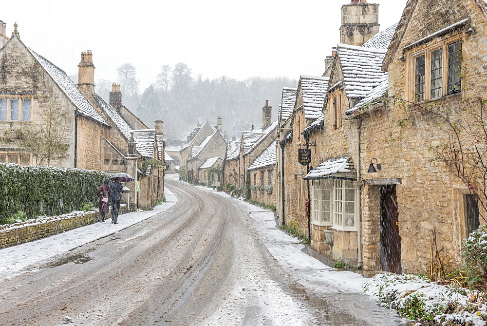 A couple walking up the hill in Castle Combe with an umbrella protecting them from the heavy snowfall, Wiltshire, England, United Kingdom, Europe - 1247-51