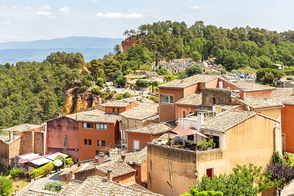 Village houses and the entrance of the Ochre trail in the background. Roussillon, Vaucluse, Provence-Alpes-Cote d'Azur, France.