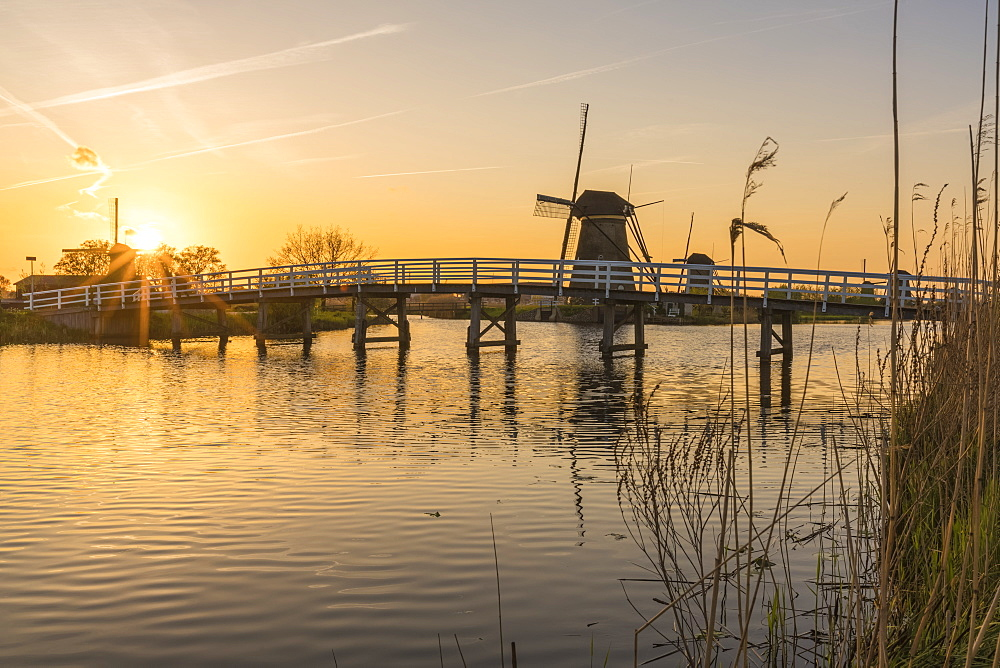 Bridge over the canal with windmills and spikes in the foreground at sunset. Kinderdijk, Molenwaard municipality, South Holland province, Netherlands.