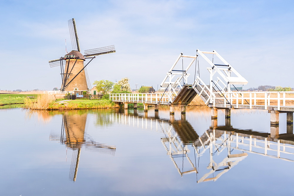 Windmill and sluice on the canal. Kinderdijk, Molenwaard municipality, South Holland province, Netherlands.