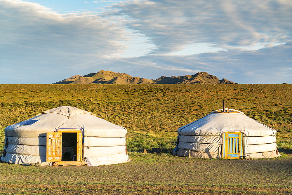 Two Mongolian nomadic gers and mountains in the background. Bayandalai district, South Gobi province, Mongolia.