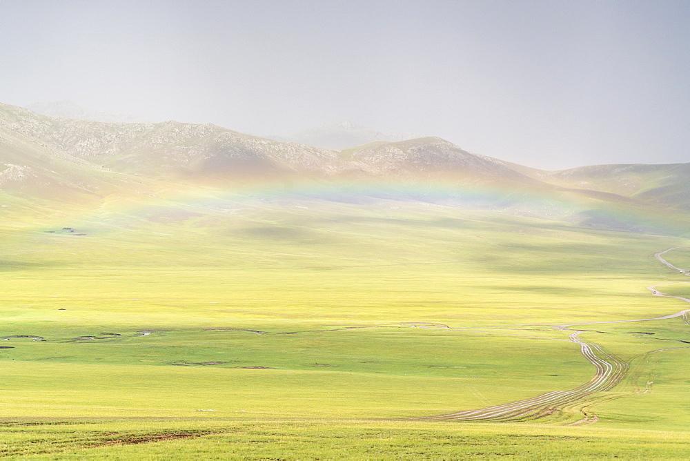 Rainbow over the green Mongolian steppe. Ovorkhangai province, Mongolia.