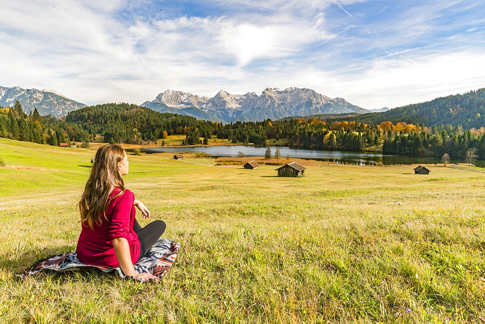 Woman sitting and staring at Gerold lake and Karwendel Alps, Krun, Upper Bavaria, Bavaria, Germany, Europe - 1251-398