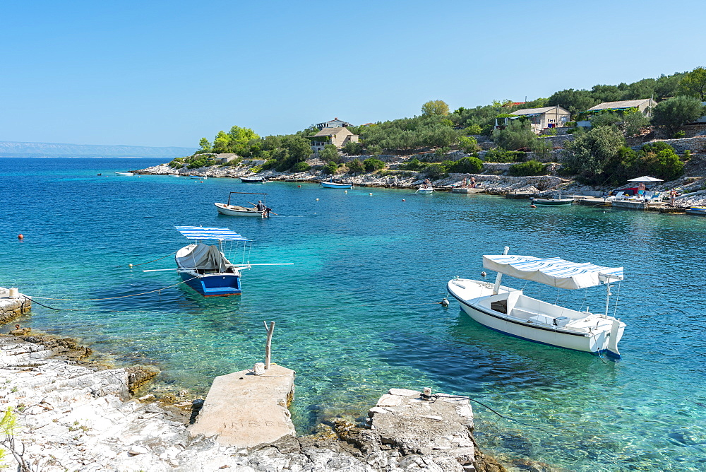 Boats at the little pier of Tankaraca cove in summer. Vela Luka, Korcula island, Dubrovnik - Neretva county, Croatia.