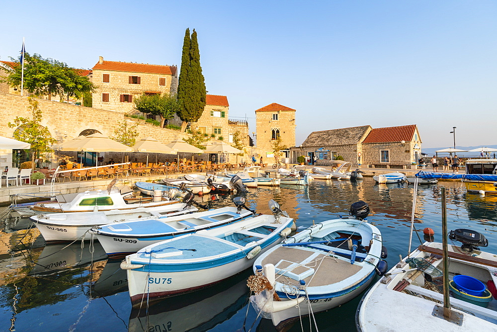 Boats at the pier of the town at sunset, Bol, Brac island, Split-Dalmatia county, Croatia, Europe