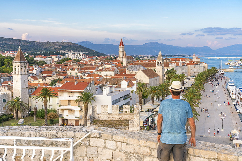 Man with hat admiring the old town from Karmelengo castle, in summer, Trogir, Split-Dalmatia county, Croatia, Europe